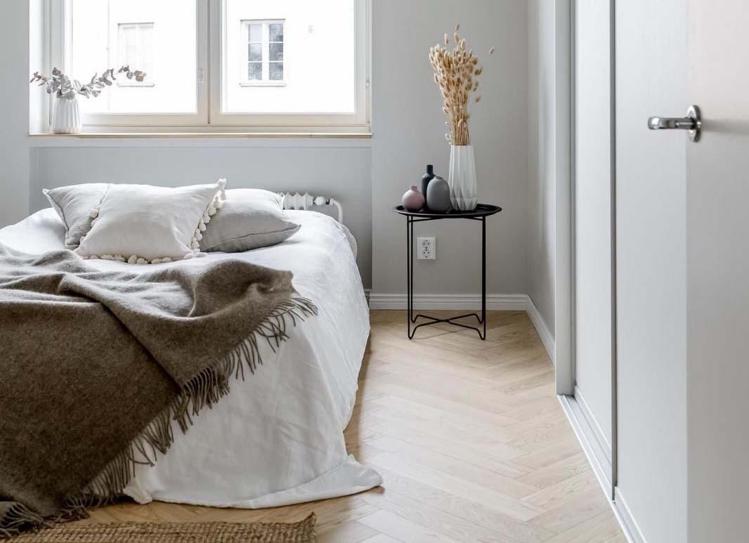 Kaunis makuuhuone, josta ylimääräiset tavarat on piilotettu ja sänky pedattu